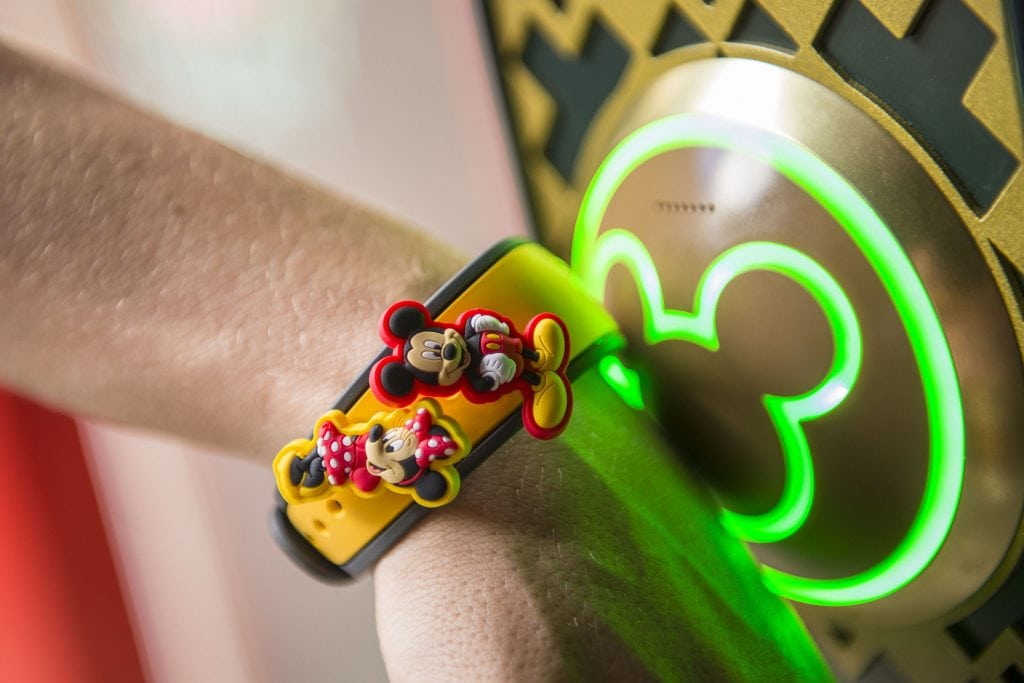 Person wearing a yellow bracelet with Mickey and Minnie Mouse buttons attached