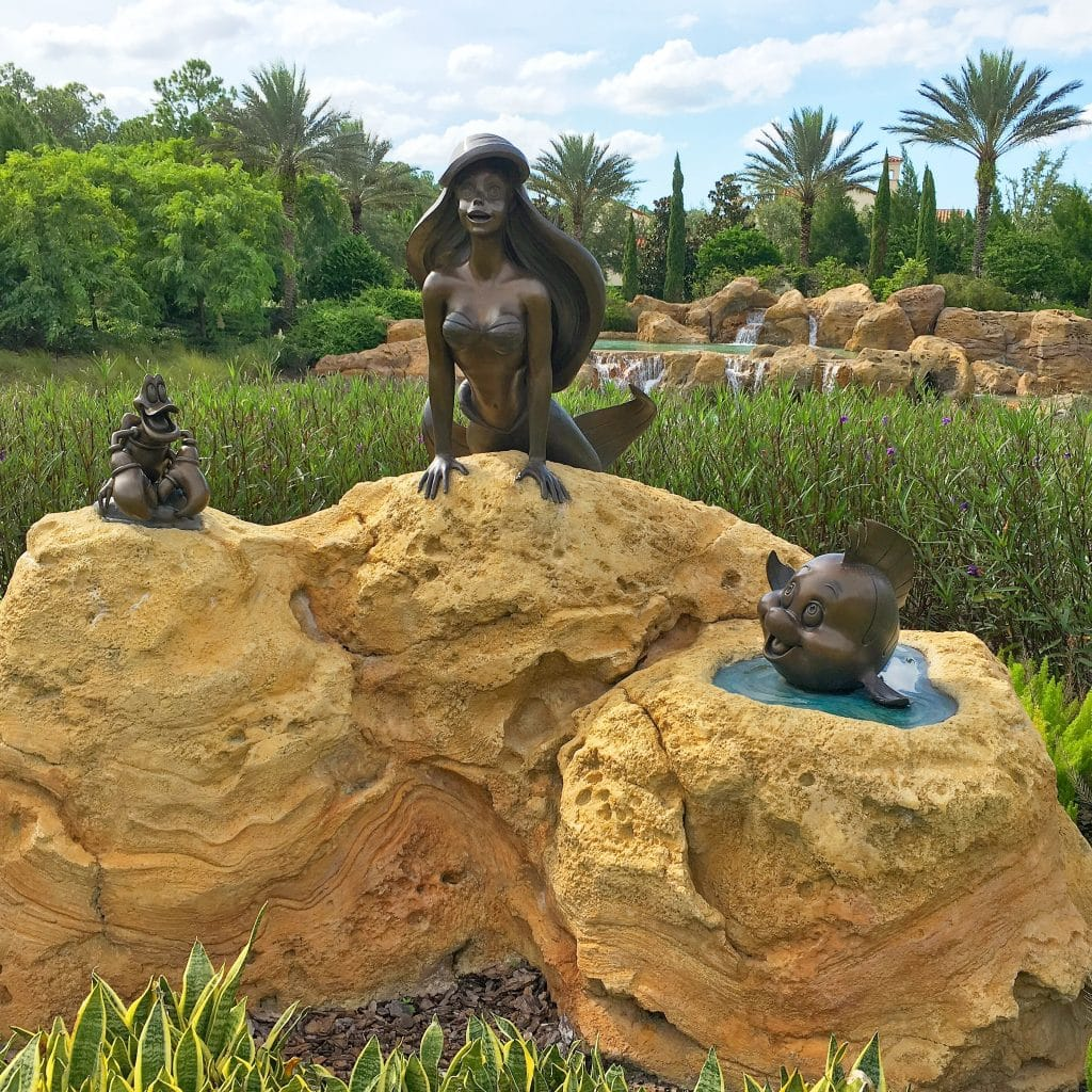 Little Mermaid and Flounder bronze statues on rock in Golden Oak Neighborhood