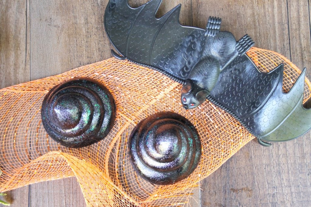 glittery black bat poop soap molds next to black plastic bat on orange tulle background