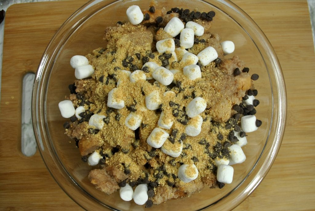 marshmallows chocolate chips graham cracker crumbs in glass bowl on wooden table