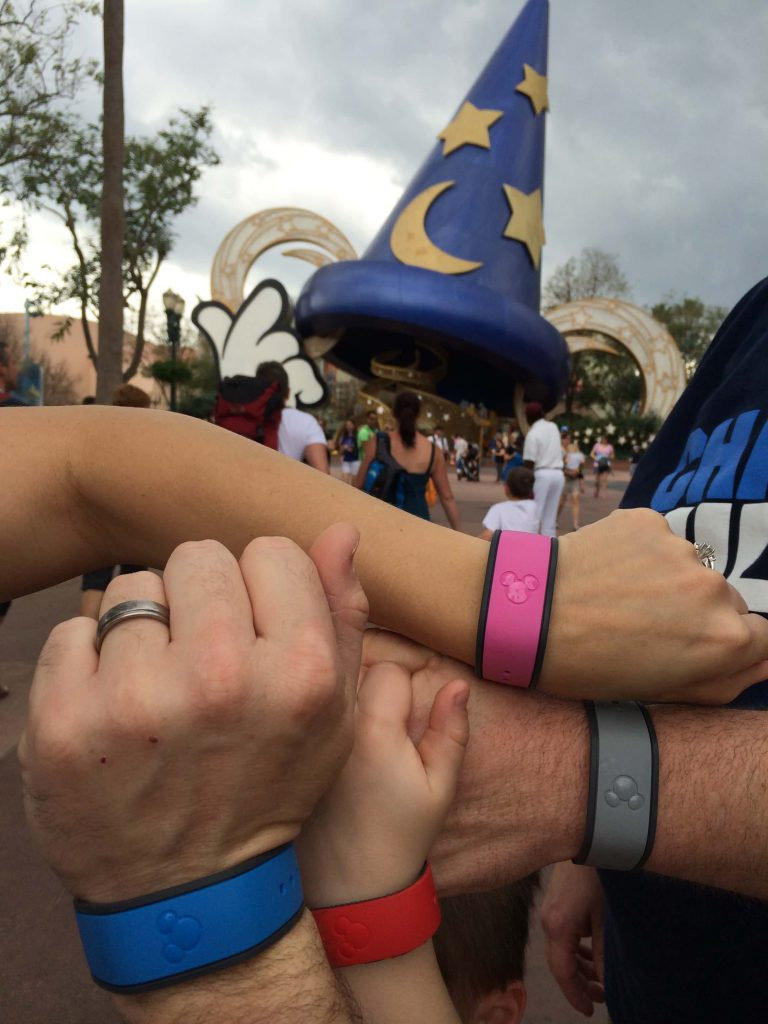 family wearing Disney MagicBands in many colors in front of Sorcer Mickey Hat