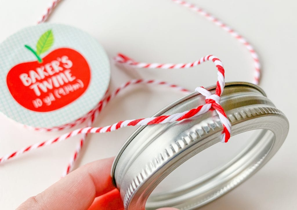 red and white bakers twine tied around canning jar lid ornament