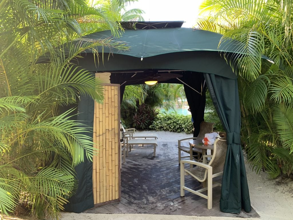 cabana surrounded by palm trees in the sand at Discovery Cove Orlando Florida