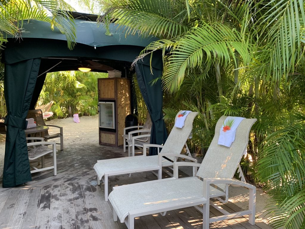 cabana surrounded by palm trees in the sand with lounge chairs at Discovery Cove Orlando Florida