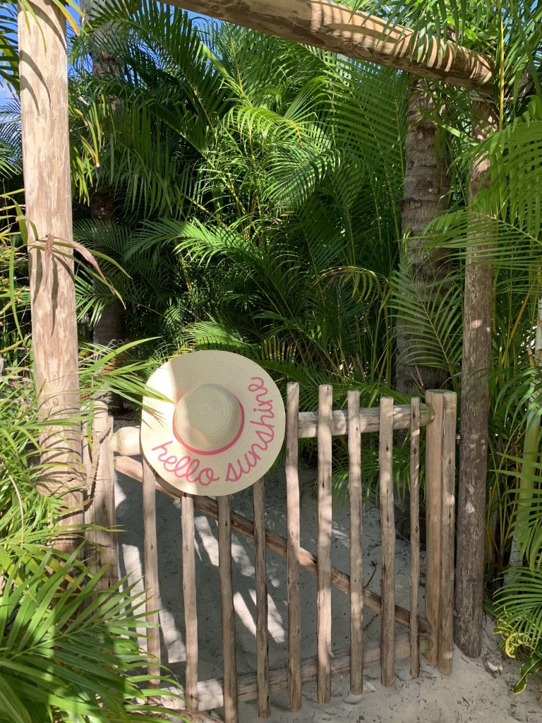 Wooden tropical gate with straw hat hanging at Discovery Cove Orlando Florida