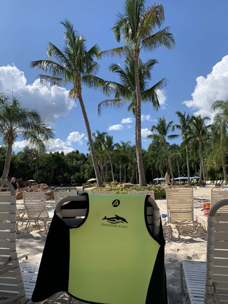 discovery cove swim vest on beach chair in sand with palm trees and blue sky Orlando Florida
