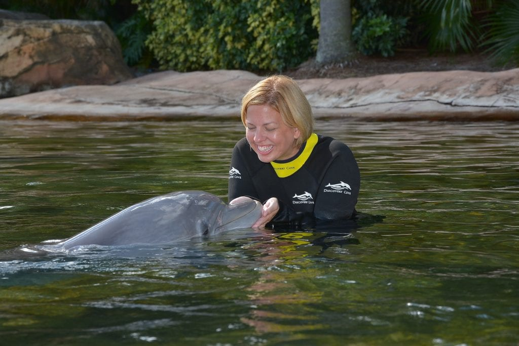 woman holding dolphin in shallow water and smiling Discovery Cove Orlando Florida