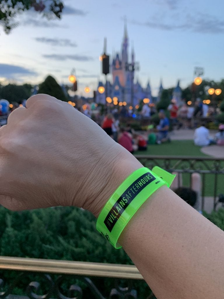 Villains After Hours Magic Kingdom Wrist band in front of Cinderella Castle