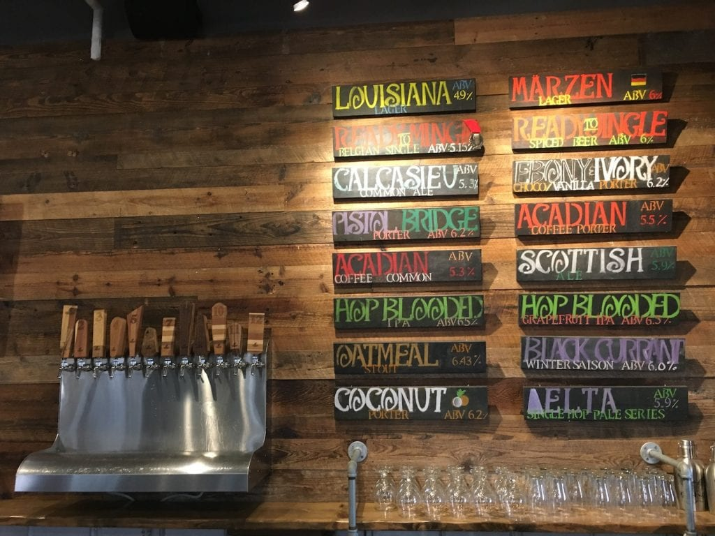 craft beers on tap wooden signs with beer names on wooden wall Lake Charles Louisiana