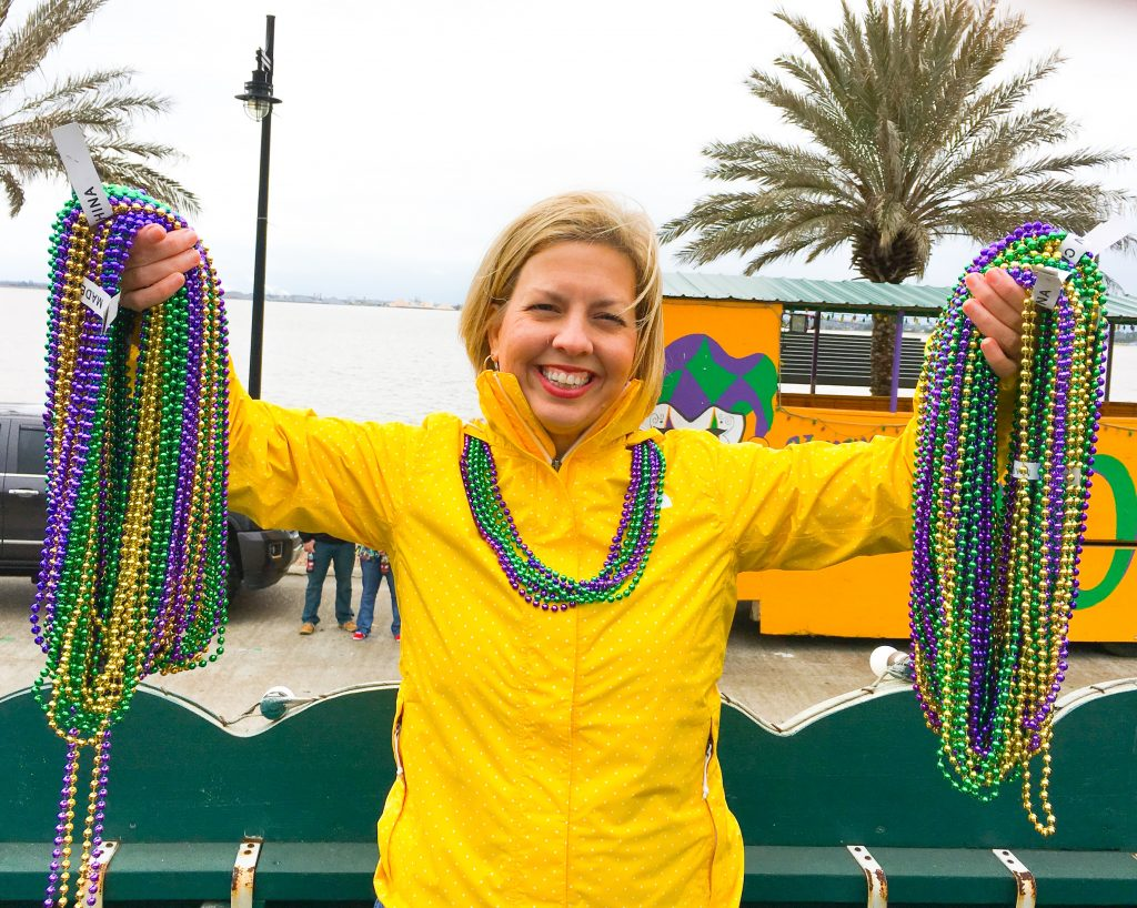 Kim holding mardi beads in hands wearing yellow jacket on lake Charles Mardi Gras parade float