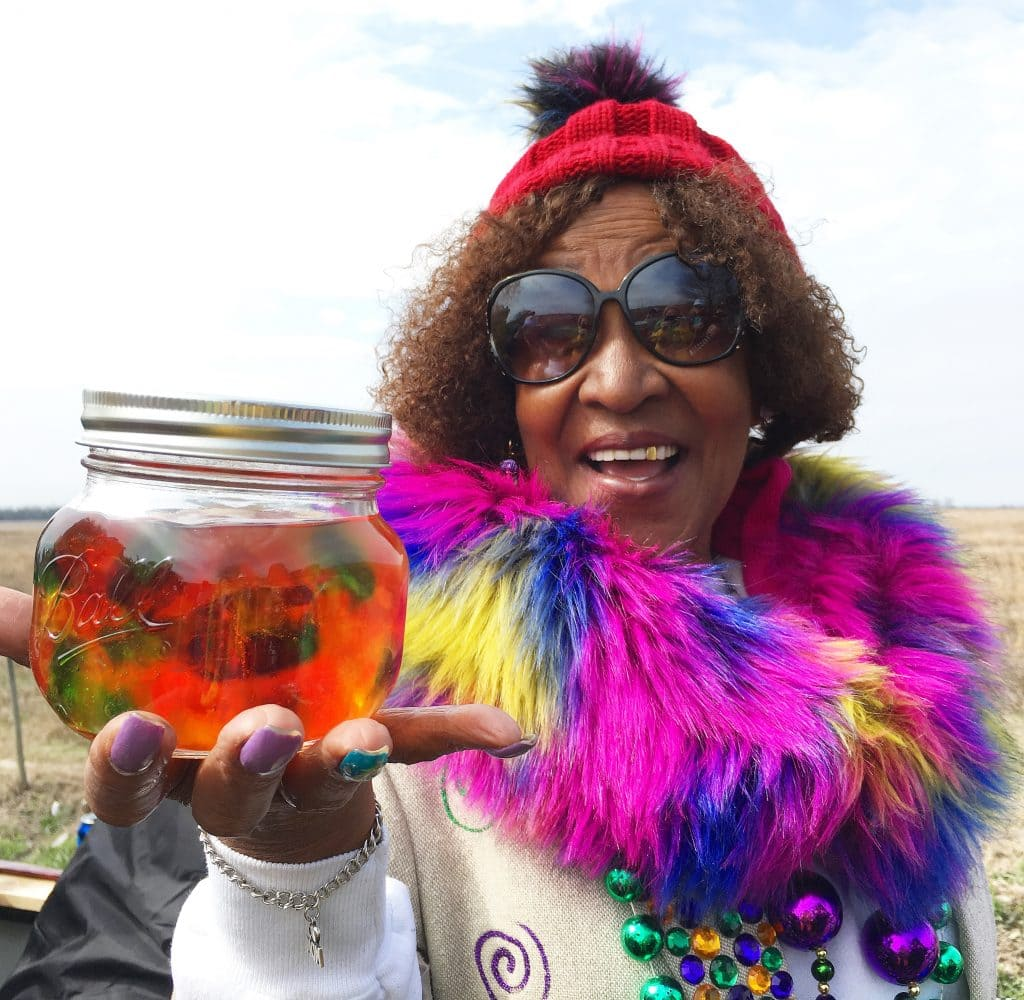 woman wearing plink boa holding mason jar full of tequila and gummy worms