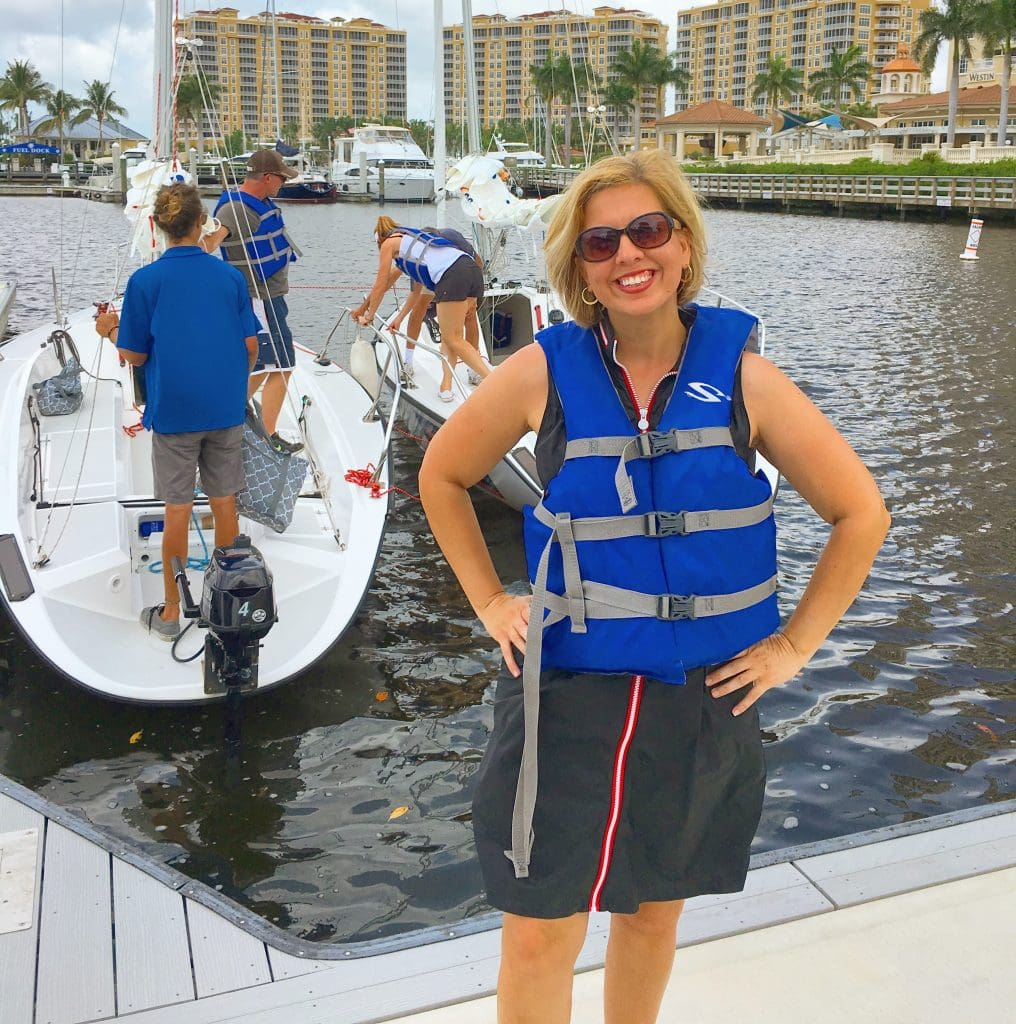 woman in life jacket standing on dock in marina in front of offshore sailing school boat Cape Coral FL