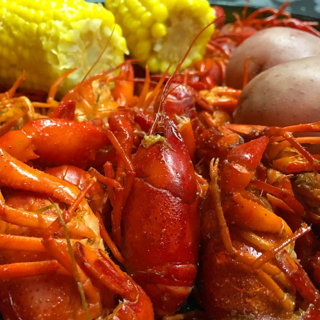 crawfish, potatoes and yellow corn in a cast iron pot