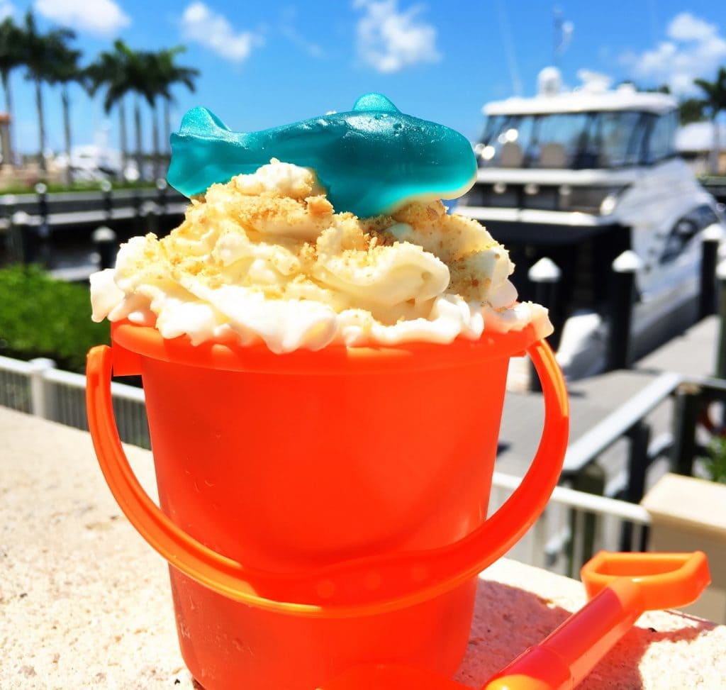 orange plastic sand pail filled with ice cream and topped with whipped cream with blue candy shark on top against marina background at Westin cape coral fl