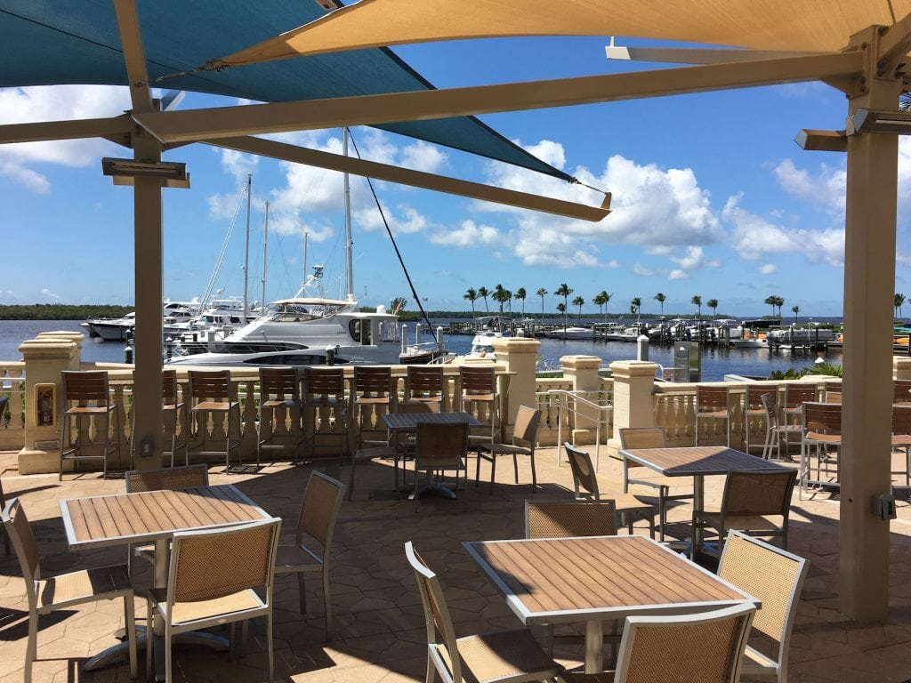 outdoor restaurant seating by water in marina