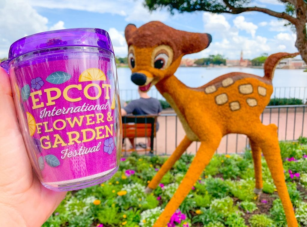 purple Epcot flower and garden festival tumbler mug in front of Bambi topiary