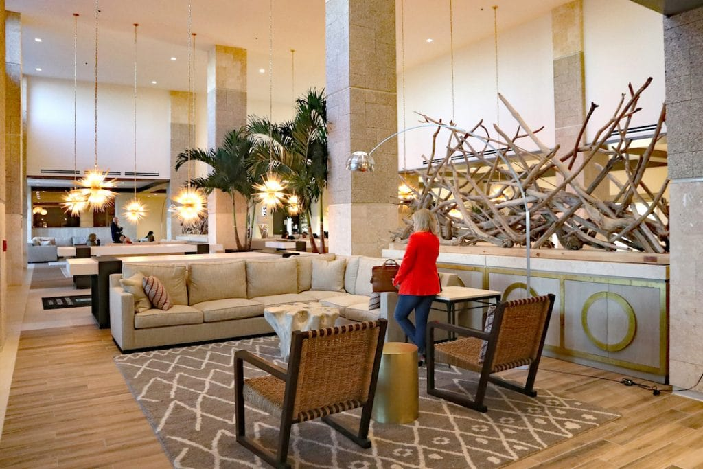 woman in red jacket standing in embassy suites st. Augustine beach lobby with coastal decor