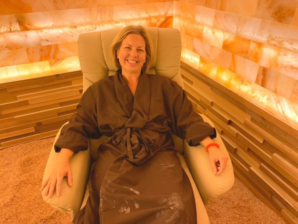 woman in brown robe sitting in lounge chair in Himalayan pink salt therapy room