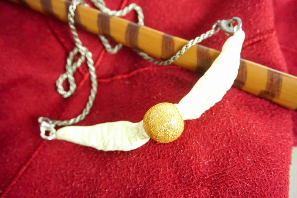 golden snitch ball with wings necklace on red background with wand