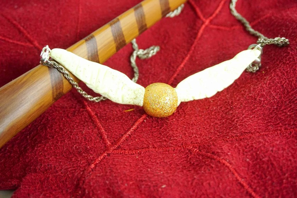 Golden Snitch Ball with Wings Necklace on red background with Harry Potter wand