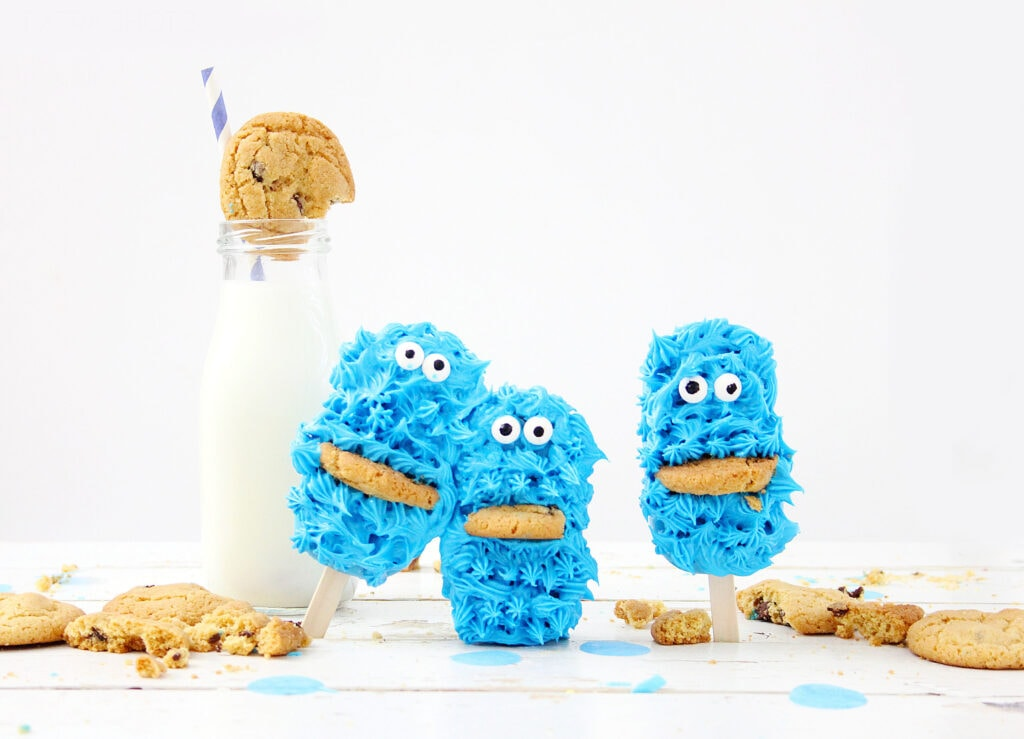 Cookie Monster cake pops next to glass bottle of milk