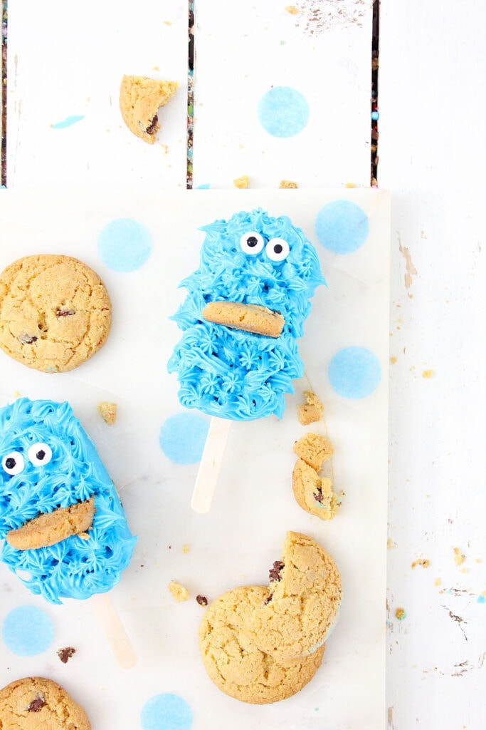 Cookie Monster cake pops on white background with chocolate chip cookies