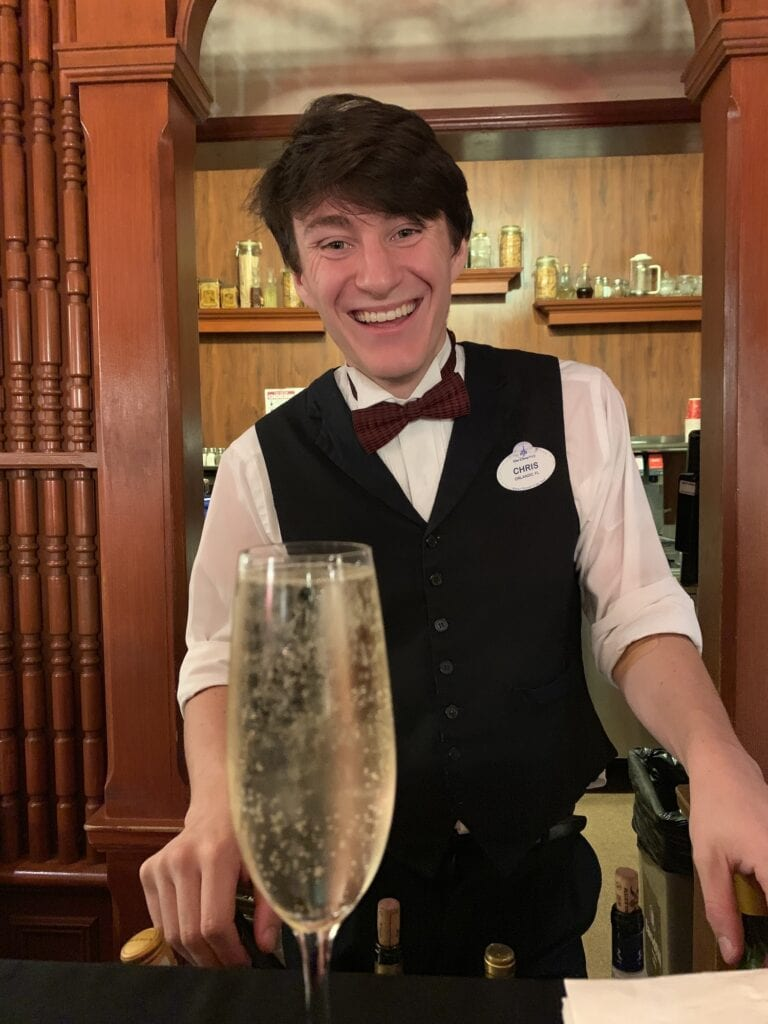 disney bartender with glass of Prosecco at cruella's halloween hide away party