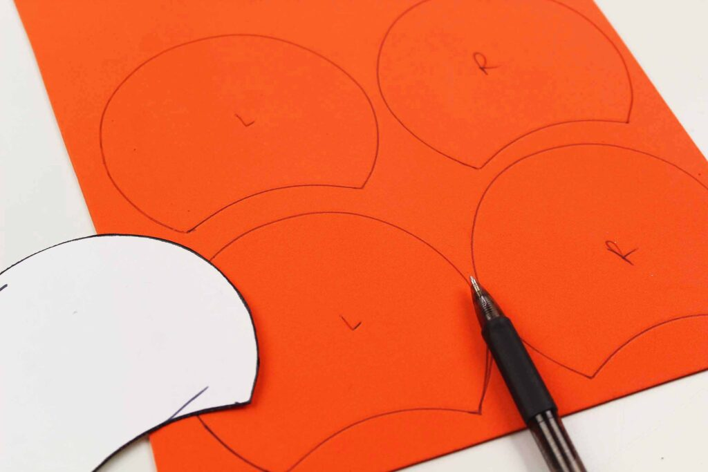 tracing a Mickey Mouse ear template on orange foam