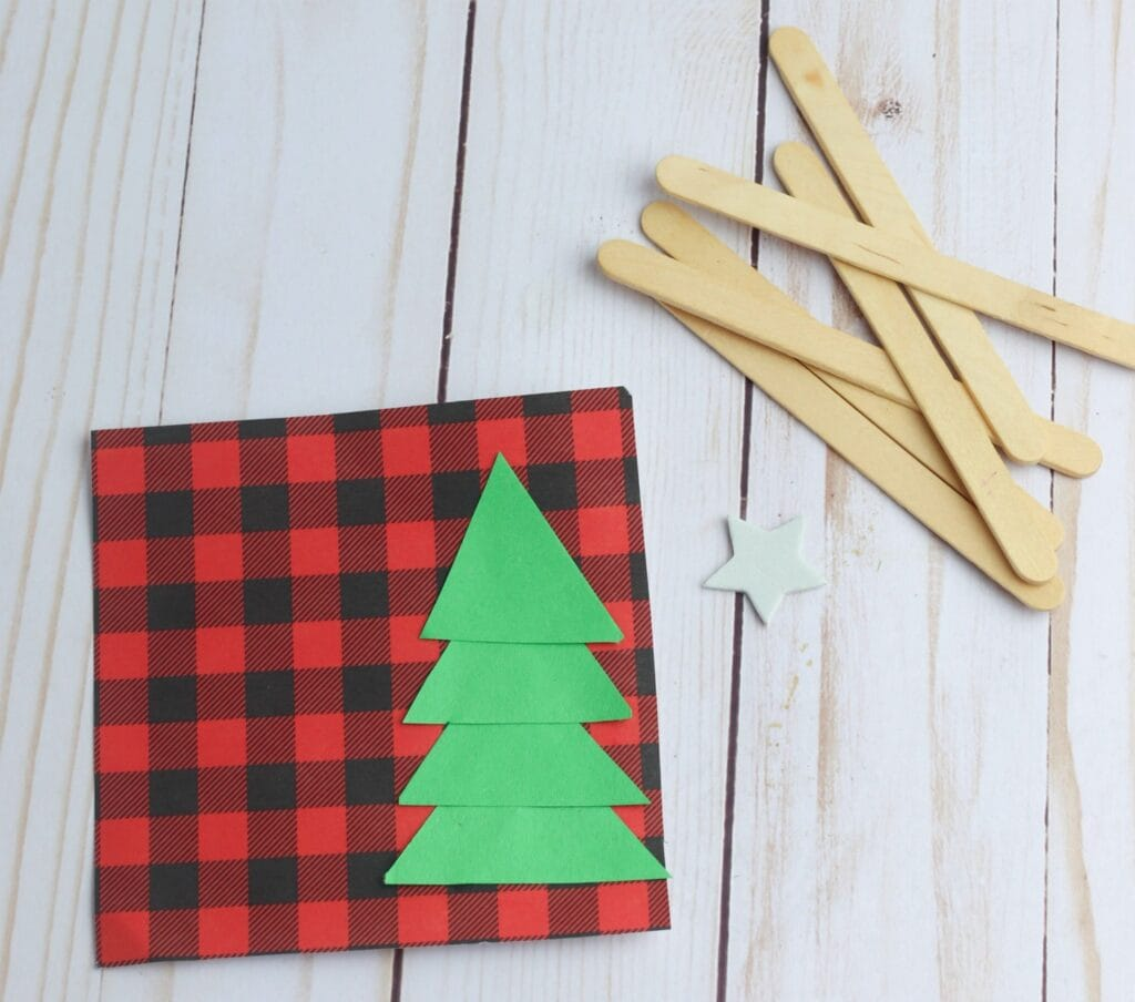 green construction paper Christmas tree on buffalo check plaid background