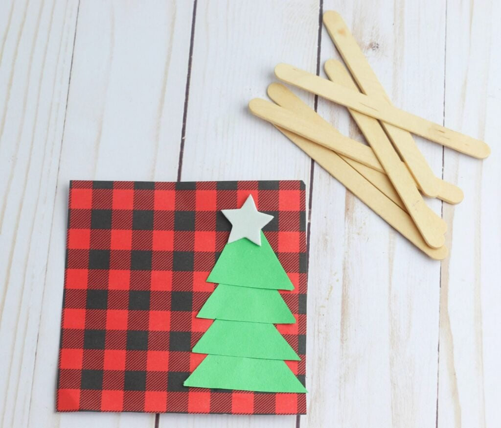 star on top of green construction paper Christmas tree on plaid square