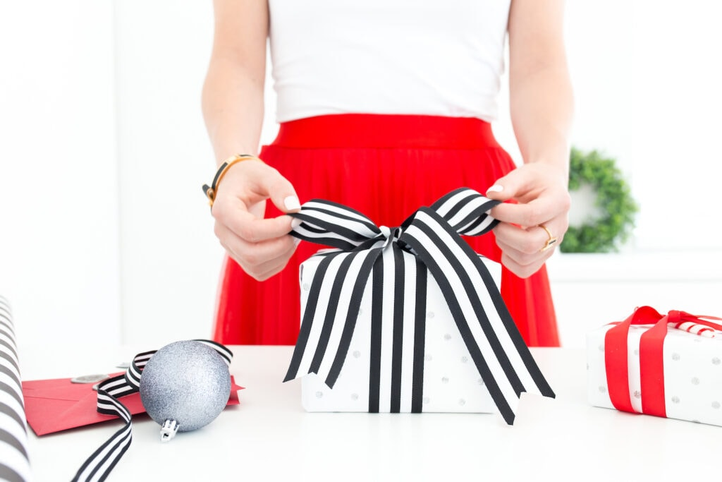 woman wearing red skirt tying black and white striped bow on a present