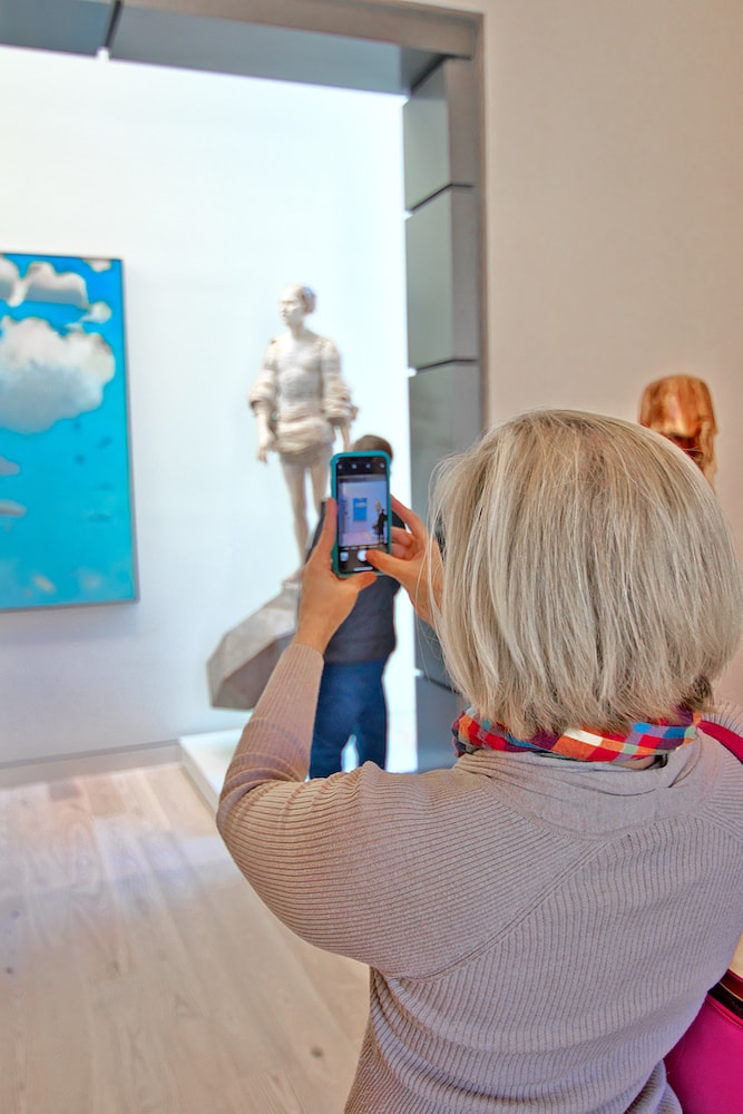 woman taking a photo of art with cell phone