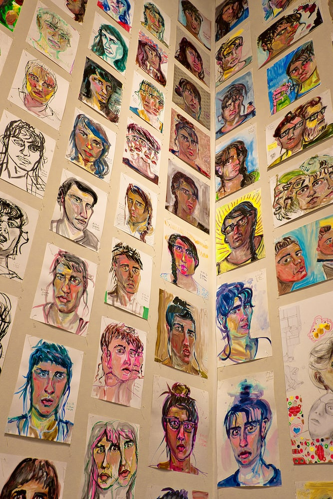 self portrait drawings hung on a wall