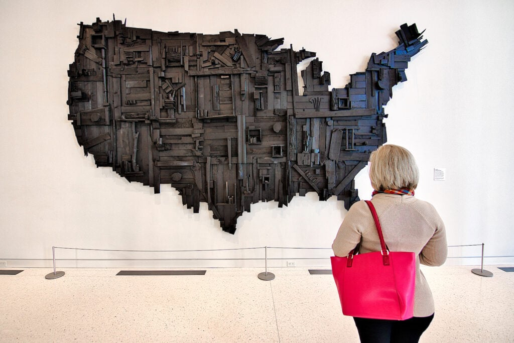 woman holding pink purse looking at wooden United States artwork