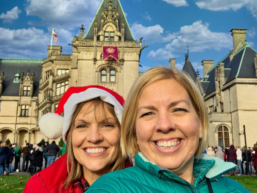 two women wearing jackets in front of Biltmore House