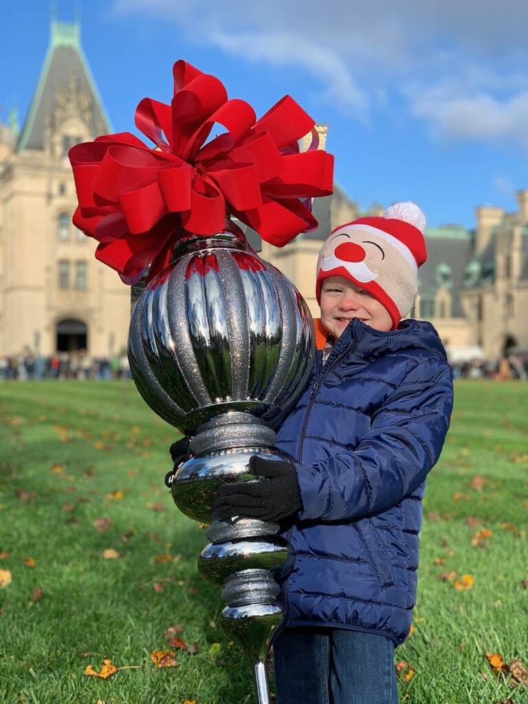 boy holding large Biltmore Christmas ornament in front of house