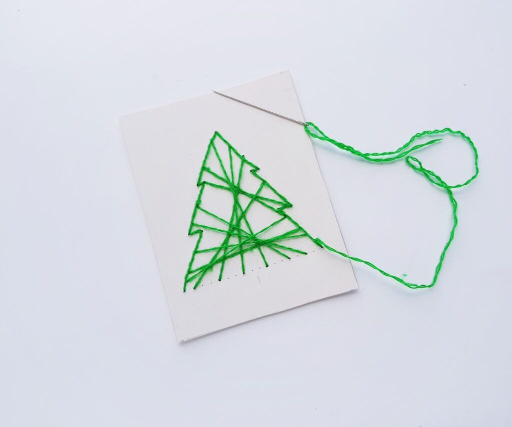 christmas tree stitched with green yarn on white paper