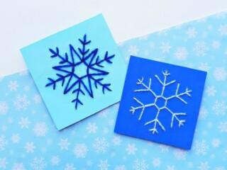 snowflake string art on blue cardstock