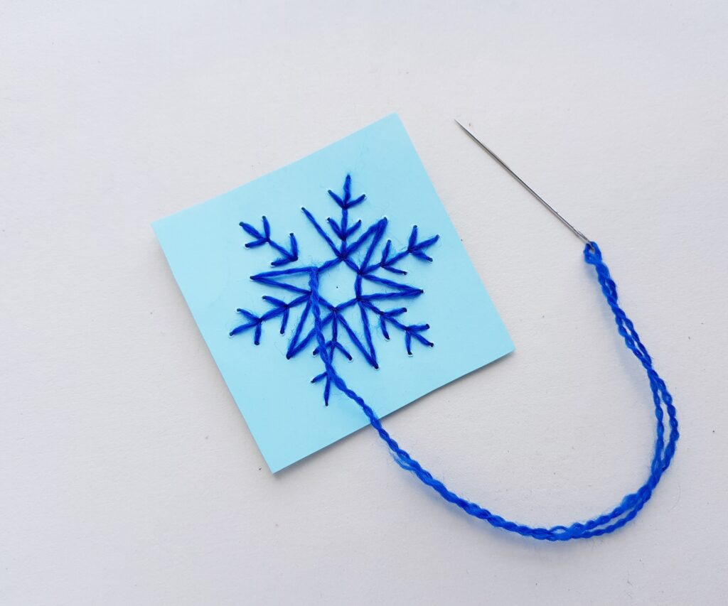 snowflake string art on blue paper