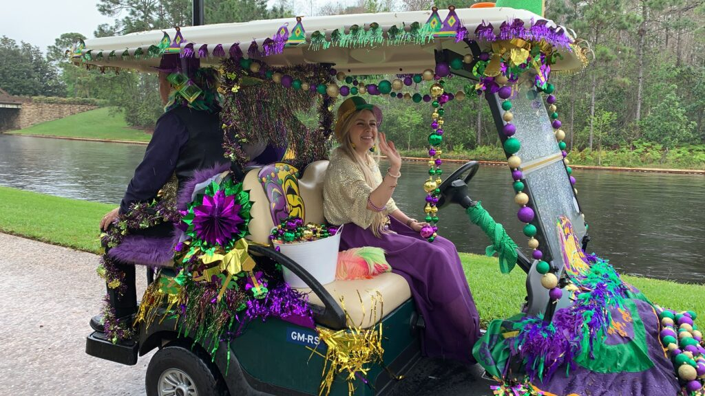 woman riding in Mardi Gras parade float golf cart