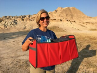 woman holding red vehicle organizer for car trunk or truck