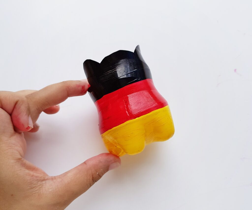plastic bottle painted in black red and yellow