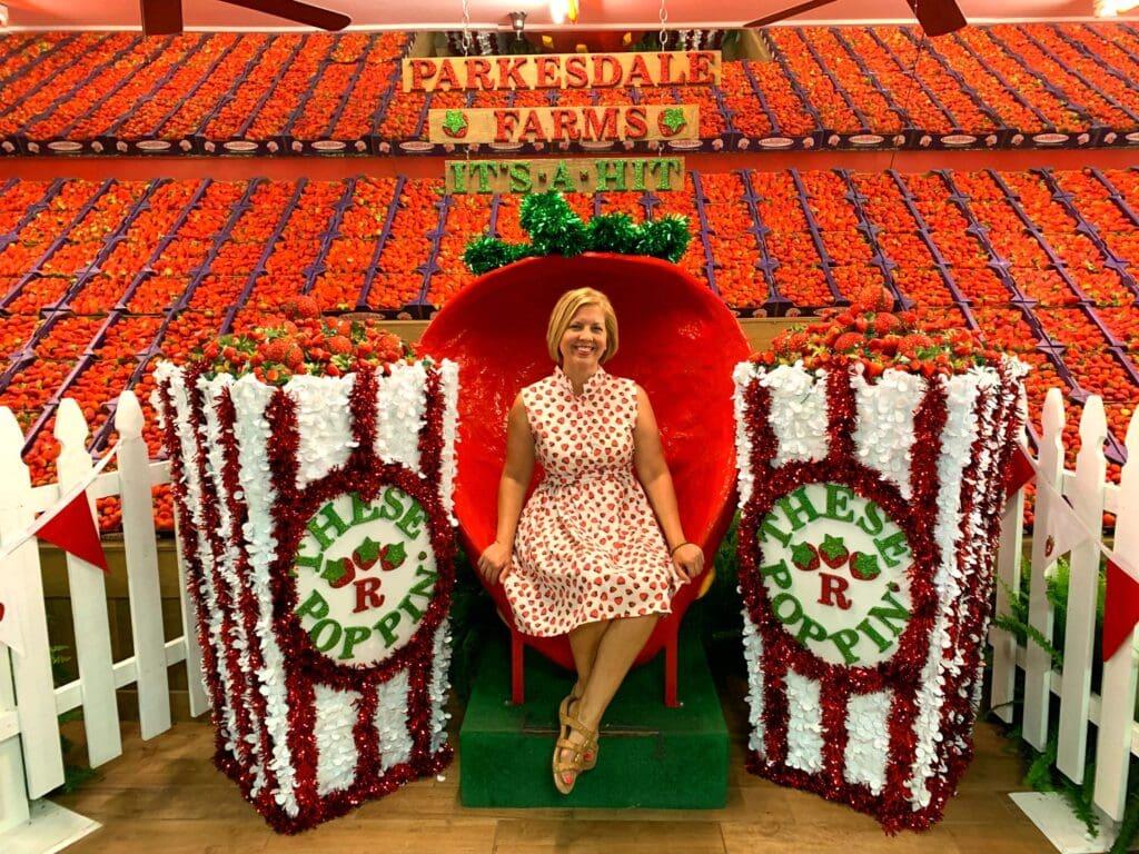 woman sitting among bushels of strawberries