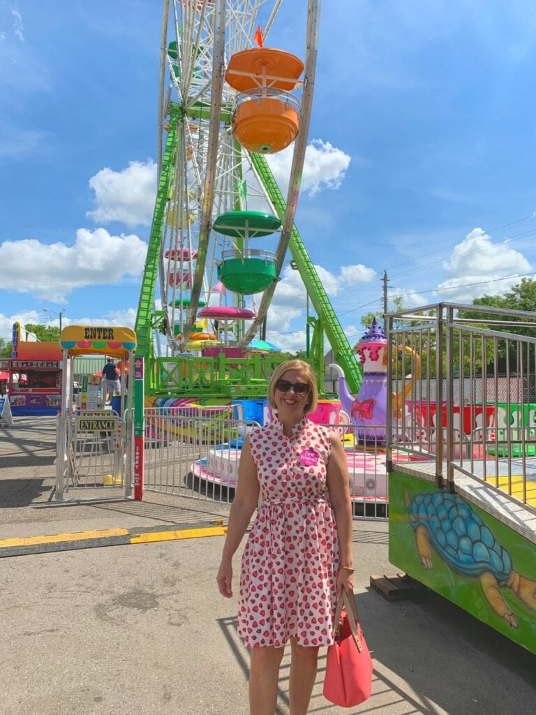 woman standing in front of Ferris wheel at Florida strawberry festival
