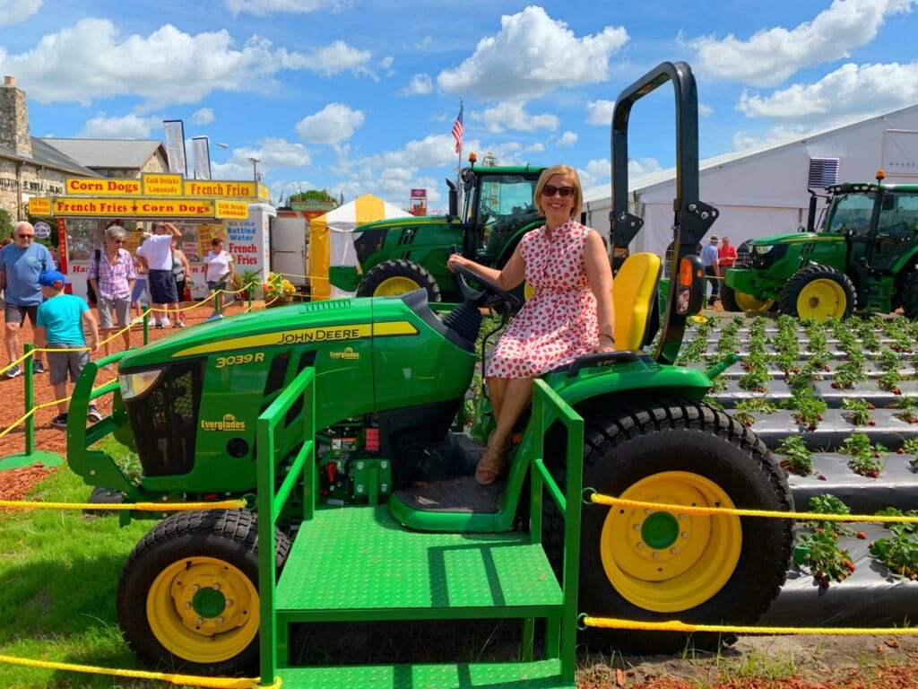 woman sitting on John Deere tractor in strawberry field