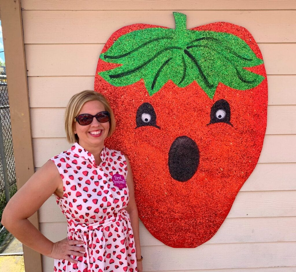 woman standing next to strawberry art on wall