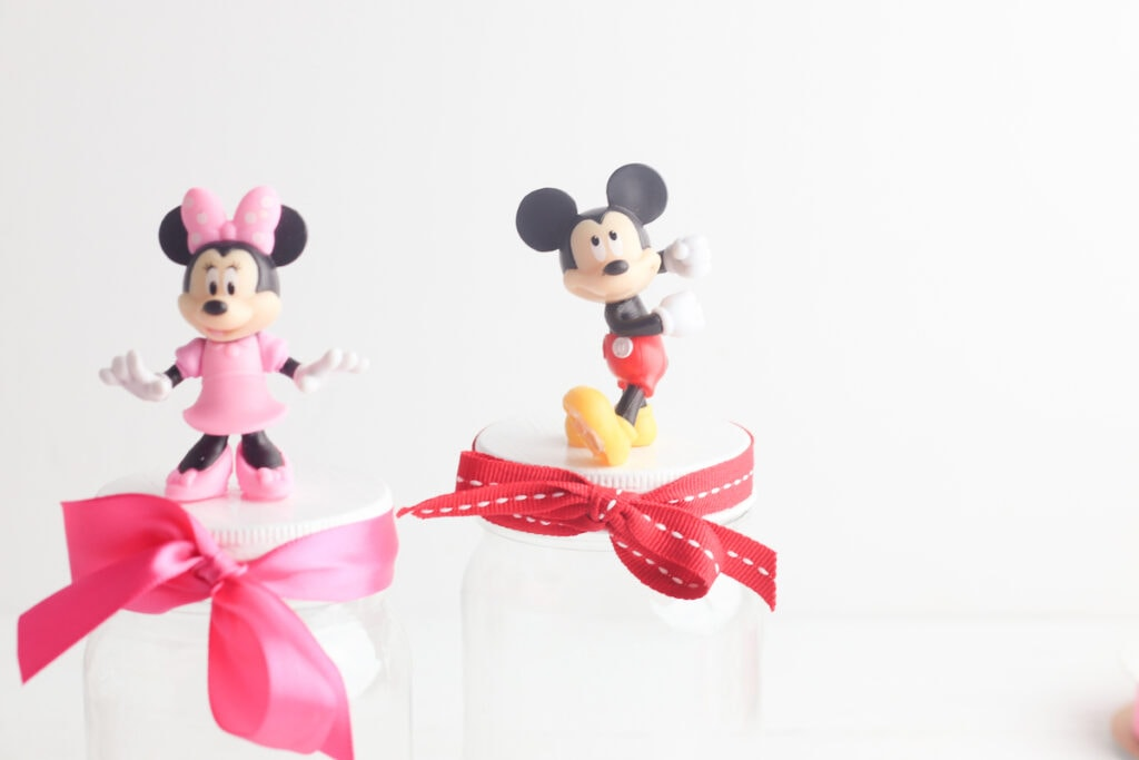 Mickey and Minnie Mouse figurines on storage jars