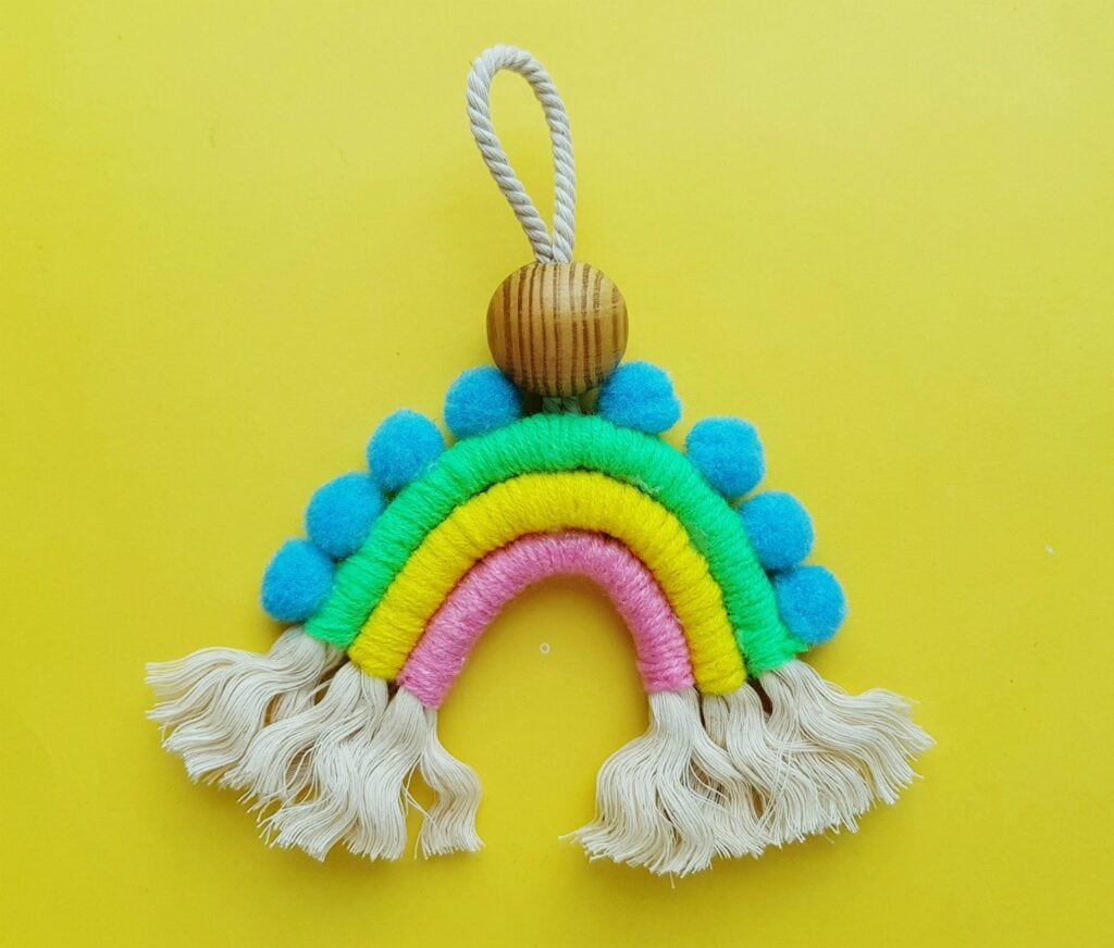macrame rainbow craft against yellow background