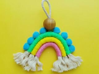 macrame rainbow craft against yellow background