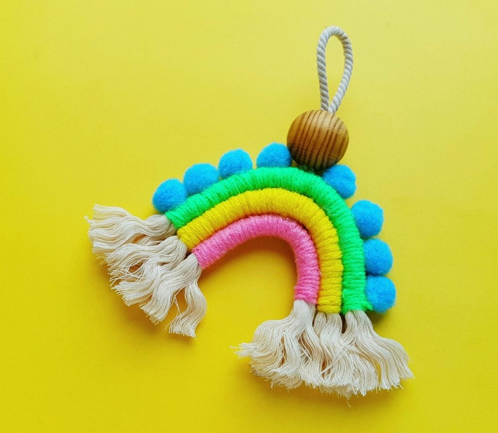 bright colored yarn wrapped rope in a rainbow shape against yellow background